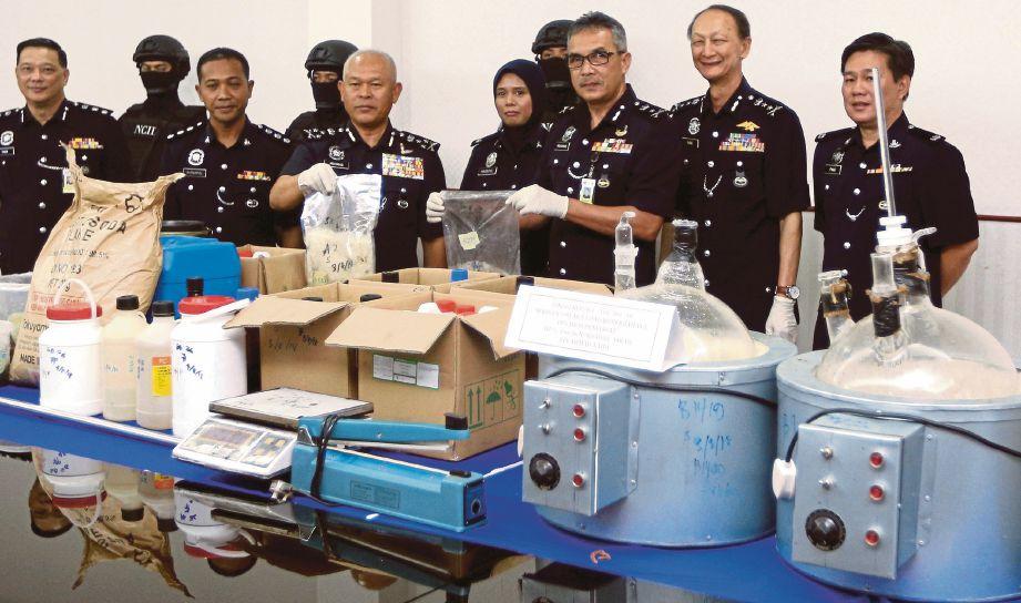 MOHMAD (tiga dari kiri) menunjukkan peralatan memproses dadah  syabu yang dirampas.