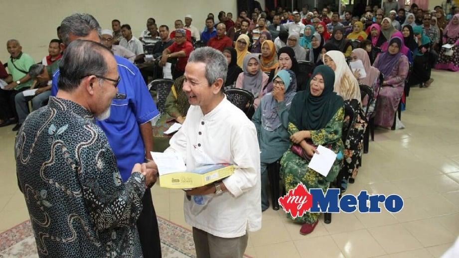 MUHMMAD (kiri) menyerahkan sumbangan kepada ibu bapa yang mewakili anak mereka. FOTO Ismail Muhamad