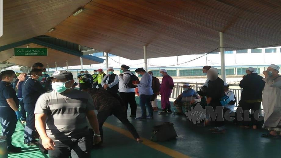JEMAAH tabligh diiring pihak berkuasa sebaik tiba di Terminal Feri Tawau sebelum diserahkan kepada MKN. FOTO Ihsan pembaca.