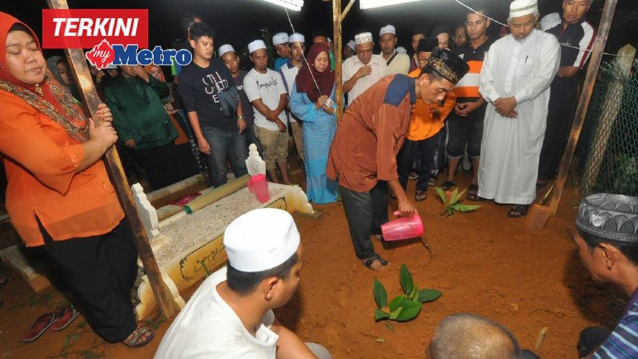 ABANG sulung Allahyarham Mohd Lazi Mohd Taher, Nor Azman, 47, menyiram air mawar di pusara tiga beranak. FOTO Muhammad Hatim Ab Manan