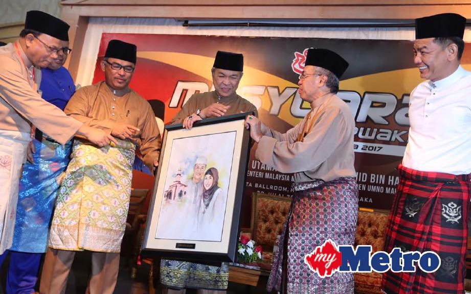 Ketua UMNO bahagian Kota Melaka, Datuk Latiff Tamby Chik (dua dari kanan) menyampaikan cenderamata kepada Timbalan Perdana Menteri, Datuk Seri Dr Ahmad Zahid Hamidi (tiga dari kanan) sambil diperhatikan Ketua Menteri, Datuk Seri Idris Haron (tiga dari kiri) pada Majlis Perasmian Mesyuarat Perwakilan UMNO Bahagian Kota Melaka di Hotel Mahkota, Banda Hilir. FOTO Rasul Azli Samad