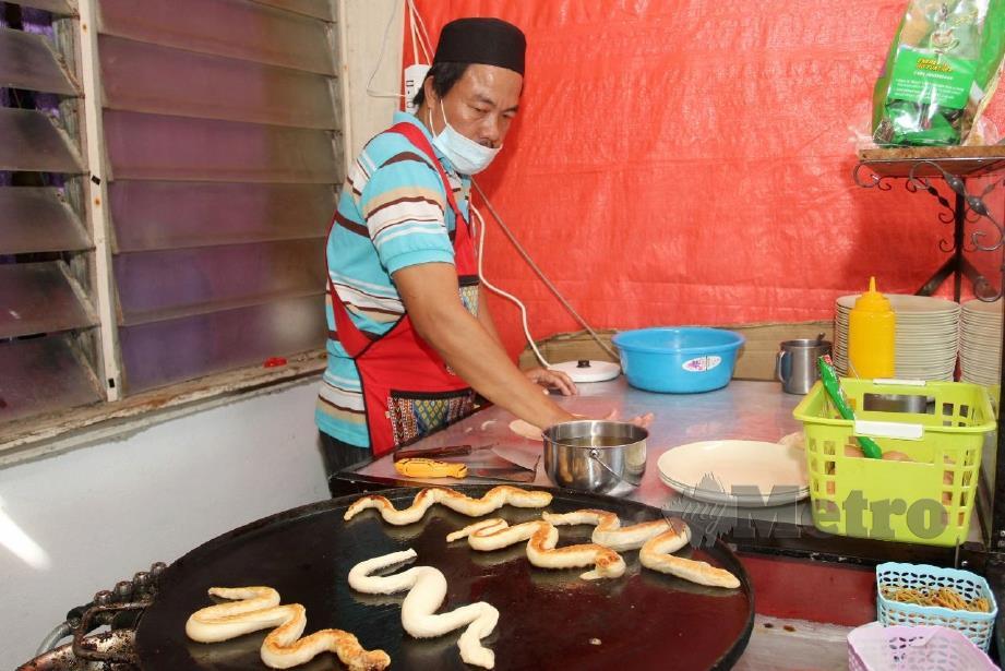 CHE Harun menyediakan 'roti canai ular' di kedainya. FOTO Nik Abdullah Nik Omar