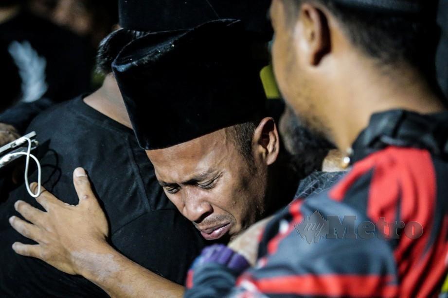Achey tidak dapat menahan kesedihan selepas Abam selamat dikebumikan di Tanah Perkuburan Islam Jalan Sungai Pusu. FOTO/ASYRAF HAMZAH