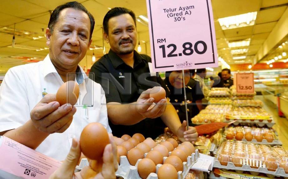 ABDUL Halim (kiri) bersama Mohd Ridzuan menunjukkan telur ayam dijual di Sunshine Square, Bayan Baru, hari ini. FOTO Ramdzan Masiam.