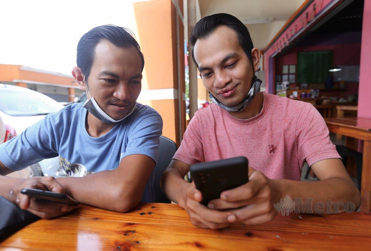 AMIRUL Hafizan (kiri) bersama Mohamad Syafiq Haikal mencari rezeki sebagai penghantar makanan sejak diberhentikan kerja Mac lalu. FOTO Fathil Asri