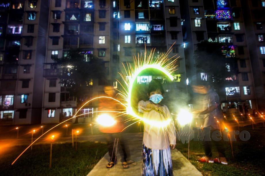 KANAK-KANAK bermain bunga api di Pangsapuri Abdullah Hukum, Kuala Lumpur, bagi menceriakan Aidilfitri di ibu negara pada ketika warga kota tidak dibenarkan melakukan perjalanan rentas negeri berikutan Covid-19. FOTO OSMAN ADNAN.