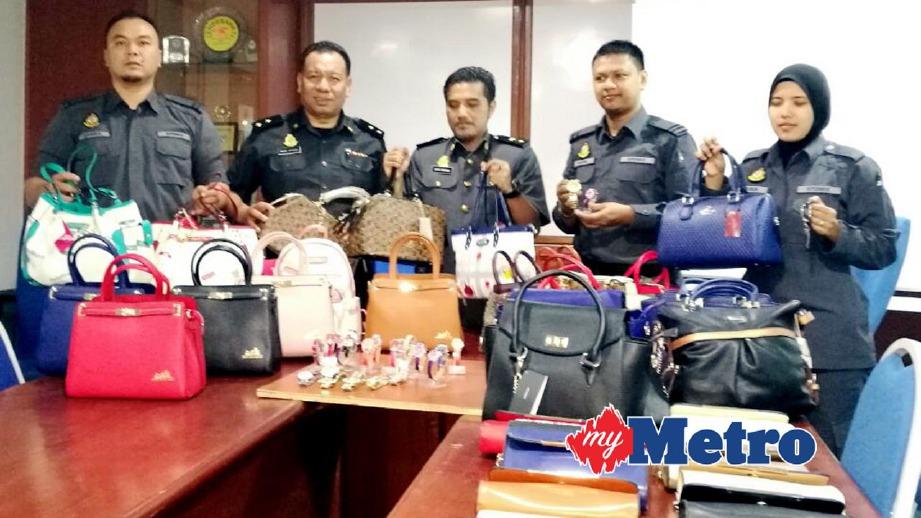 SHAARANI (tengah) menunjukkan beg serta jam tangan wanita tiruan yang dirampas. FOTO Nor Farhani Che Ad