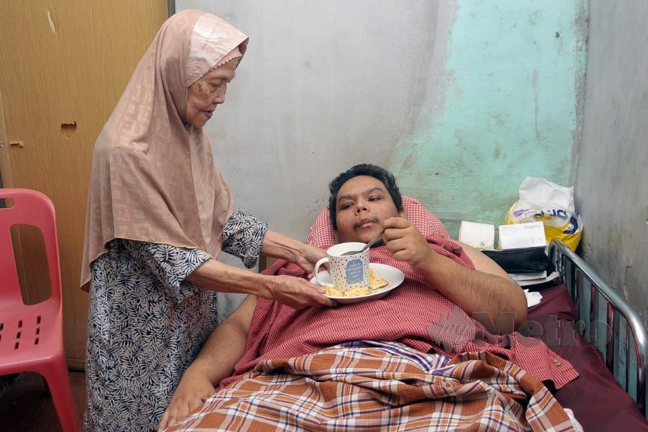 NAPSIAL menyuapkan makanan kepada Ashaari yang terlantar di rumahnya. FOTO Amran Yahya