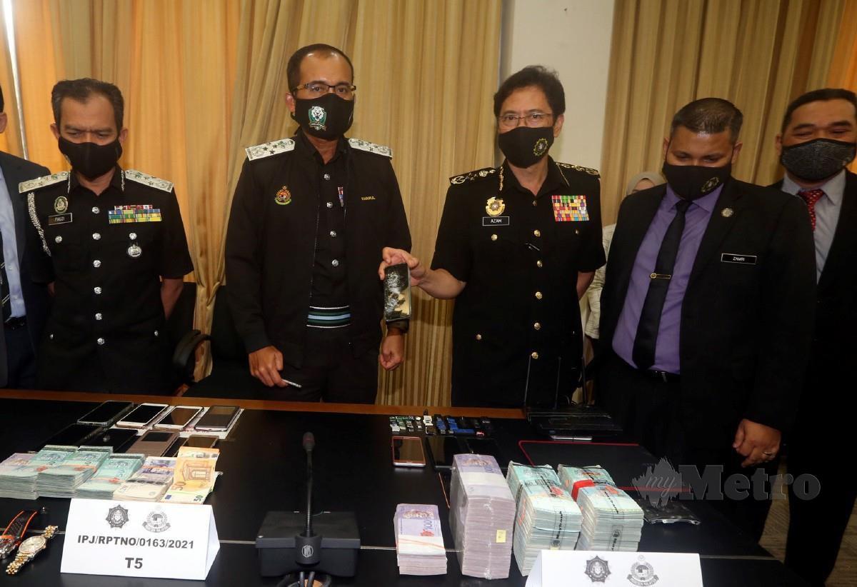 Azam (tiga dari kanan) bersama Khairul Dzaimee (tiga dari kiri) menunjukkan sebahagian sebahagian telefon bimbit, jam tangan mewah dan dan wang tunai yang dirampas ketika sidang media 'Op Hacks' di Pejabat SPRM Kuala Lumpur. FOTO Hairul Anuar Rahim