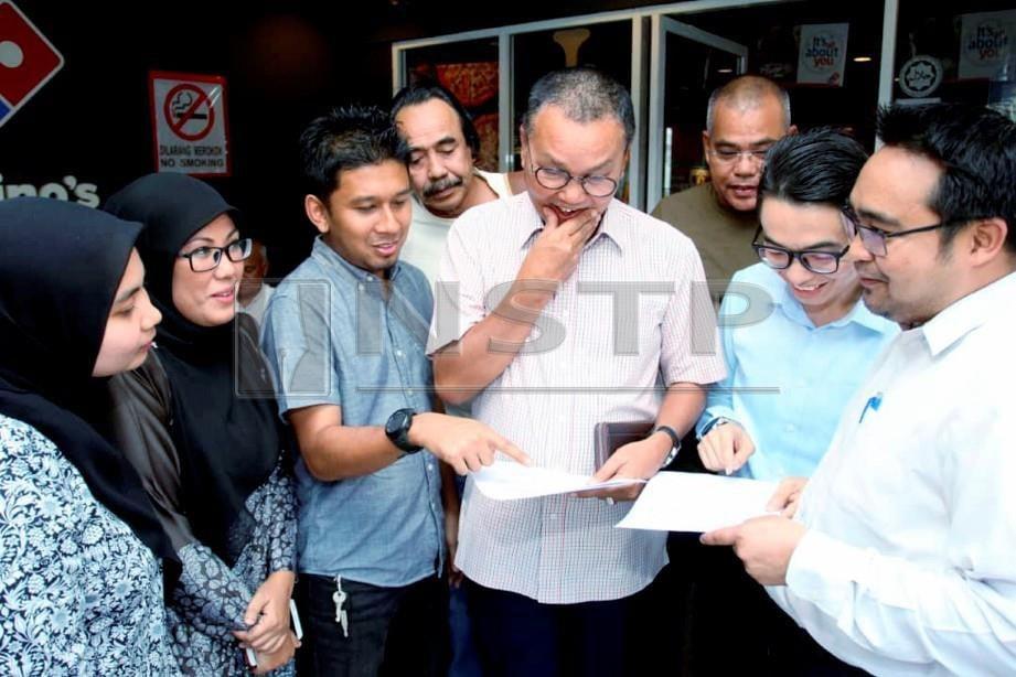 Azmi (tengah) melihat kertas saman serta surat mahkamah yang difailkan berkaitan isu kunci tayar. FOTO Nik Abdullah Nik Omar