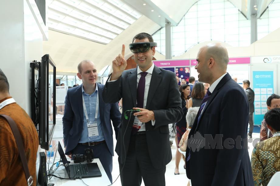 DELEGASI persidangan mencuba paparan teknologi realiti maya (VR) oleh Siemens Healthineers.