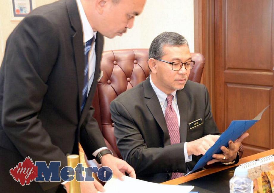 AZLAN (kanan) meneliti beberapa dokumen sebaik tiba di pejabatnya di Aras 3, Kompleks Dewan Undangan Negeri Perlis di Persiaran Wawasan untuk memulakan tugas rasmi. -Foto HAFIZUDIN MOHD SAFAR