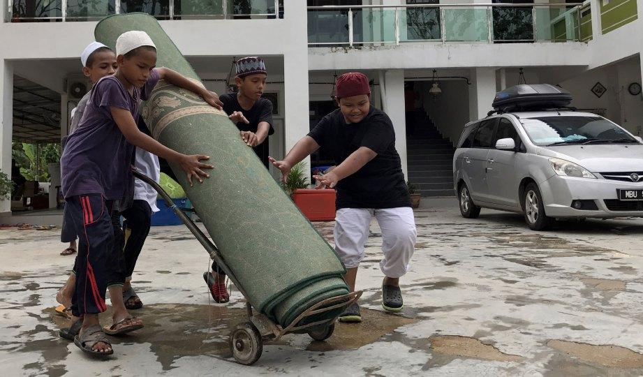 PELAJAR tahfiz bergotong-royong membersihkan peralatan di madrasah.