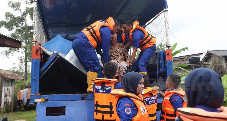ANGGOTA APM mengangkat Rafiah ke dalam lori untuk berpindah ke PPS selepas laluan ke rumahnya di Kampung Jeram Hilir, Kuala Nerus dinaiki air. FOTO Imran Makhzan.