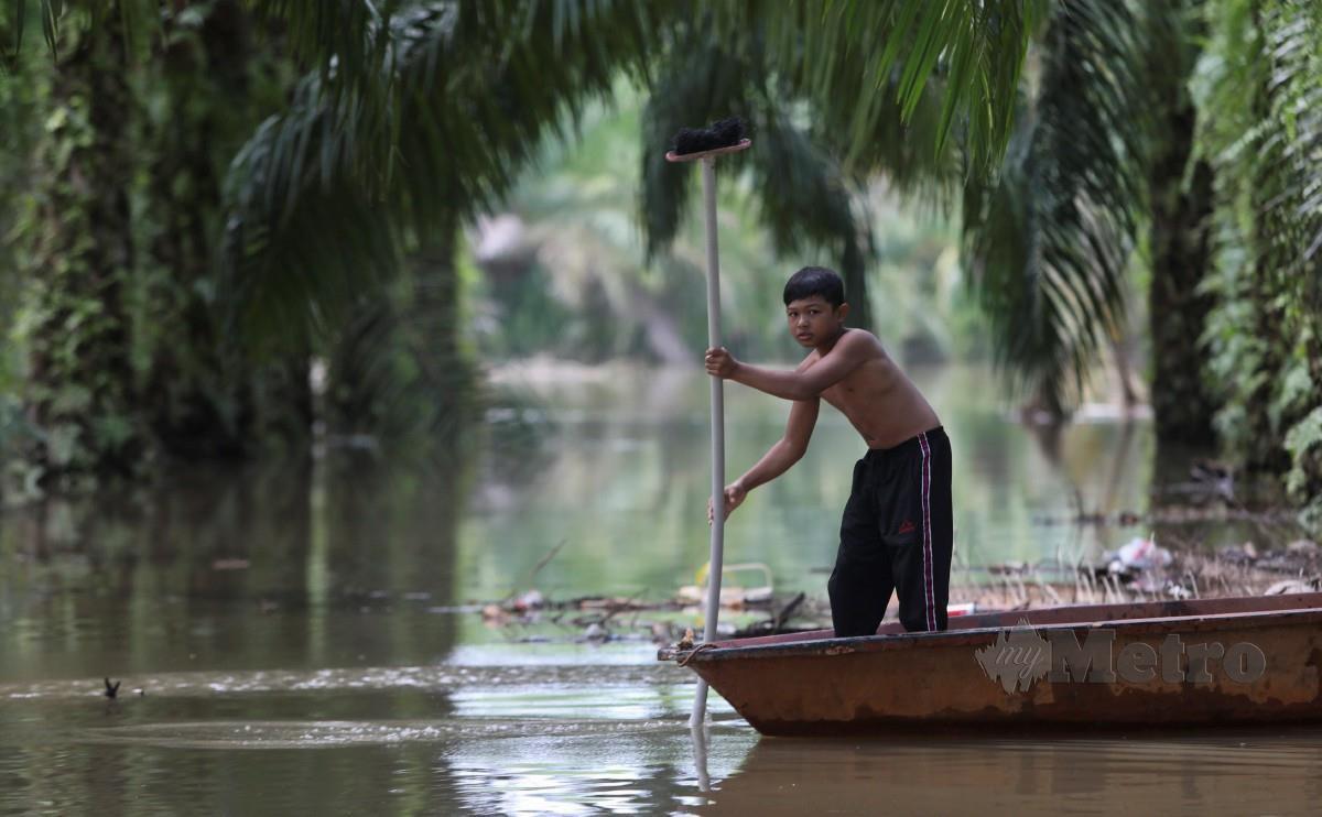KANAK-KANAK bermain air banjir di kawasan ladang sawit berhampiran rumah mereka di Kampung Tembila, Besut. FOTO Ghazali Kori.