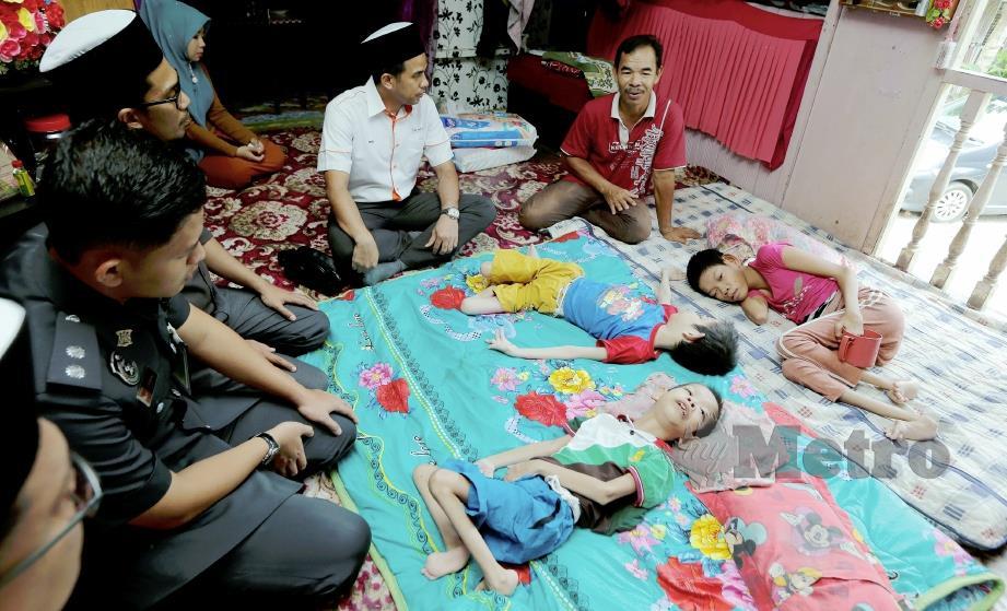 MOHD Zain (kanan) bersama Ahmad Fikri (dua kanan) di rumahnya di Kampung Kok Keli 1, Tumpat. FOTO Syamsi Suhaimi.