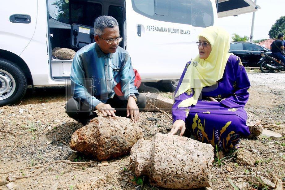 Rahimin (kiri) bersama Fadhilah menunjukkan batu nisan yang dipercayai peninggalan zaman Kesultanan Melayu. FOTO Muhammad Zuhairi Zuber