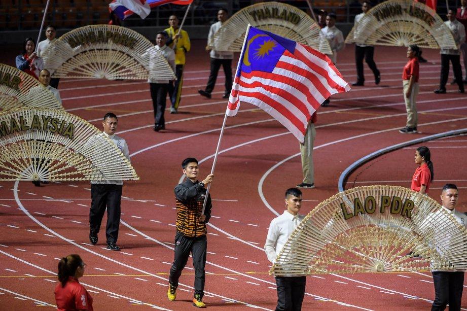 Loh Jack Chang, bekas atlet Wushu Kebangsaan membawa Jalur Gemilang pada upacara penutupan rasmi Sukan SEA Ke-30 di Stadium Olahraga New Clark City semalam. Malaysia sekadar menamatkan kempen Sukan SEA 2019 dengan kutipan 56 emas, 58 perak dan 72 gangsa untuk berada di tangga kelima keseluruhan. Vietnam akan menjadi tuan rumah Sukan SEA 2021. FOTO BERNAMA