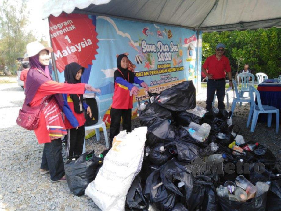 PENDUDUK setempat mengumpulkan sampah berjumlah 181.6 kilogram yang dikutip sempena program Save Our Sea di Pantai BNO. FOTO AMIRUL AIMAN HAMSUDDIN