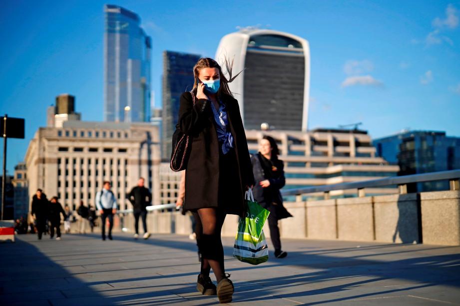 WANITA memakai pelitup muka ketika menyeberangi London Bridge, London. FOTO AFP