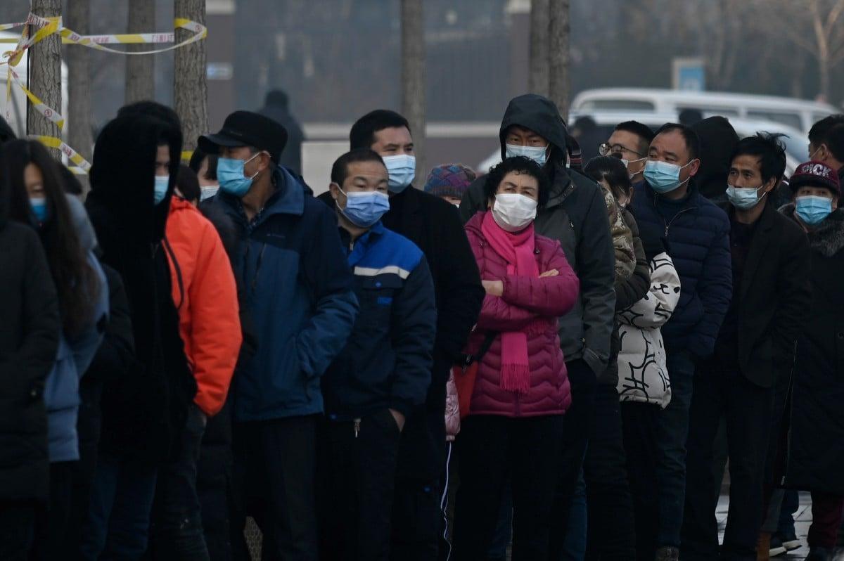 ORANG ramai beratur untuk menjalankan ujian saringan Covid-19 di wilayah Daxing, Beijing, semalam. FOTO AFP