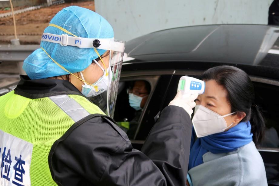 FOTO Fail menunjukkan pengawal keselamatan melakukan saringan suhu di lebuh raya di Xianning, bandar bersempadan dengan Wuhan, di utara wilayah Hubei. FOTO Reuters.