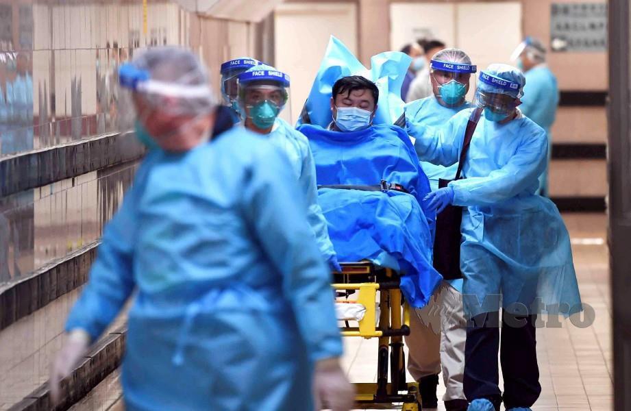 PASUKAN perubatan membawa pesakit berisiko wabak di Hospital Queen Elizabeth, Hong Kong. FOTO Reuters.
