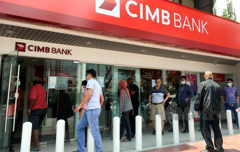 ORng ramai beratur di luar bangunan ketika berurusan di sebuah bank di Bayan Baru di sini, pada Perintah Kawalan Pergerakan bagi mencegah penularan COVID-19. FOTO Danial Saad