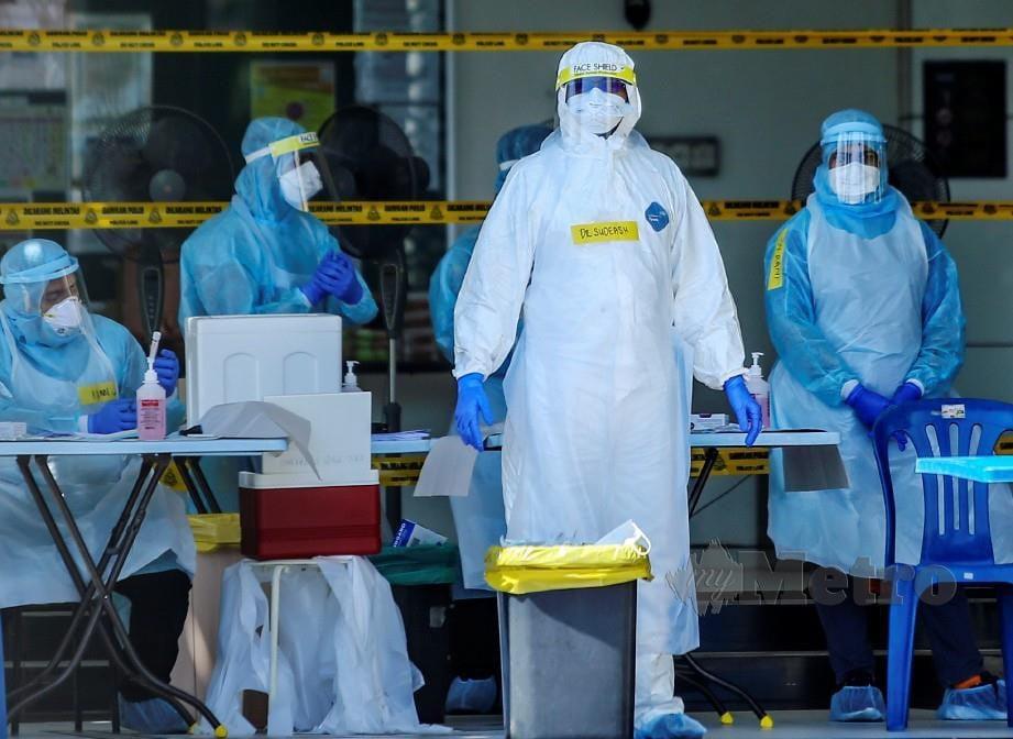 PETUGAS kesihatan dengan set lengkap PPE dan pelindung muka. FOTO Osman Adnan.