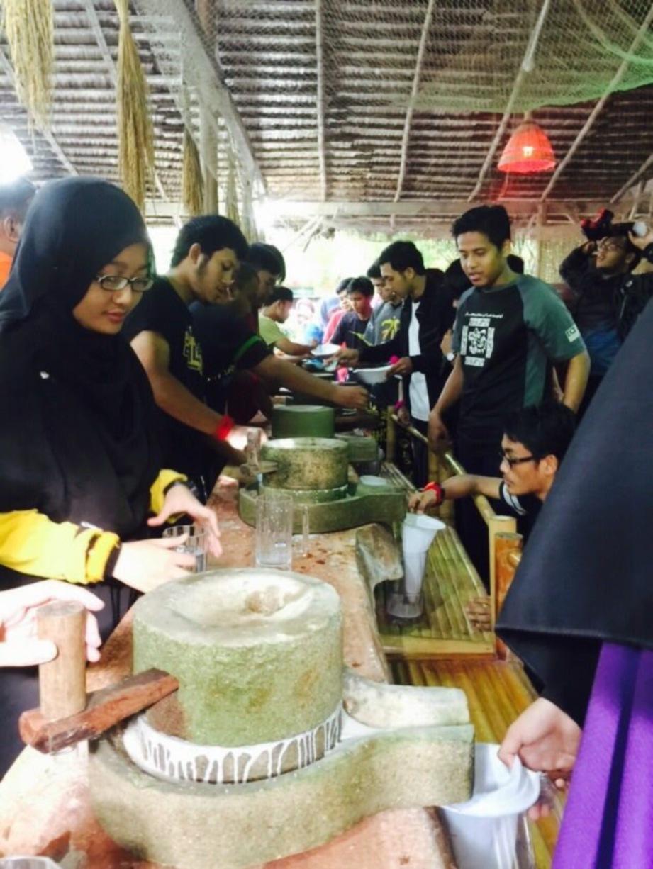 PENGUNJUNG diajar bagaimana menghasilkan kuih onde-onde secara tradisional.