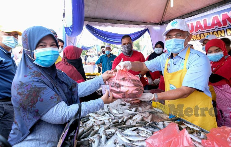 MENTERI Pertanian dan Industri Makanan Datuk Seri Dr Ronald Kiandee menyerahkan ikan kembung yang dilelong kepada pelanggan yang hadir pada Mini Karnival Industri Makanan Bukit Gantang 2020 dan Pelancaran Caruman PERKESO Nelayan di Dewan Bunga Raya Changkat Jering hari ini. FOTO BERNAMA