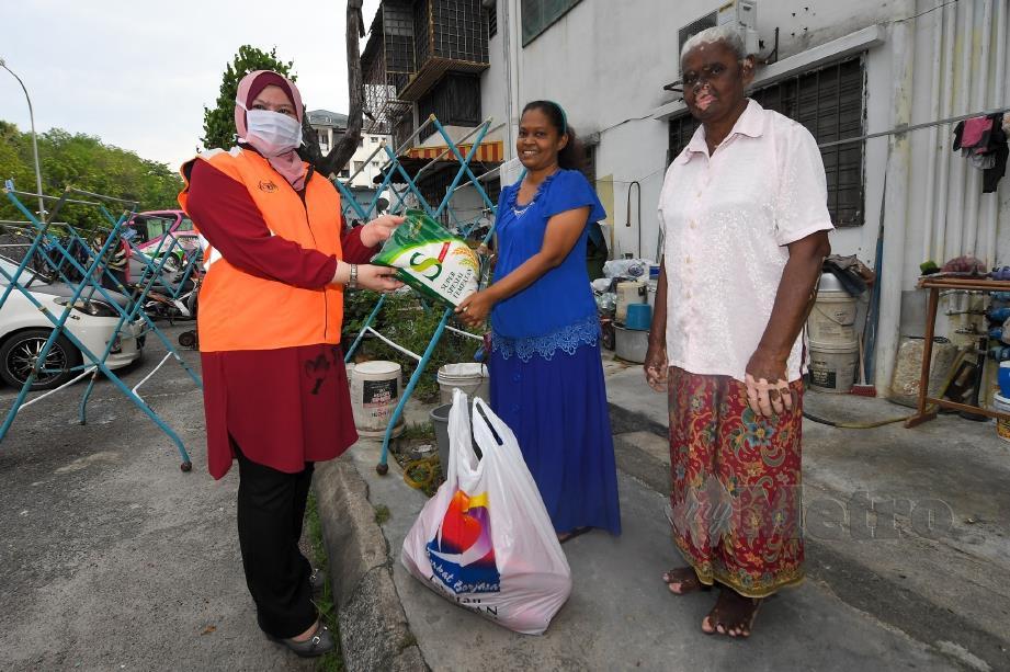 MENTERI Pembangunan Wanita, Keluarga dan Masyarakat, Datuk Seri Rina Mohd Harun (kiri) menyampaikan bantuan Bakul Makanan kepada penduduk di Flat Kos Rendah Taman Bukit Mewah, Kajang, 21 April lalu. FOTO Bernama