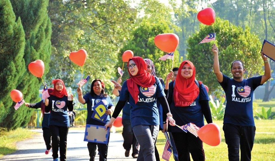 PESERTA membawa bendera semasa berjalan mengelilingi kampus UM.
