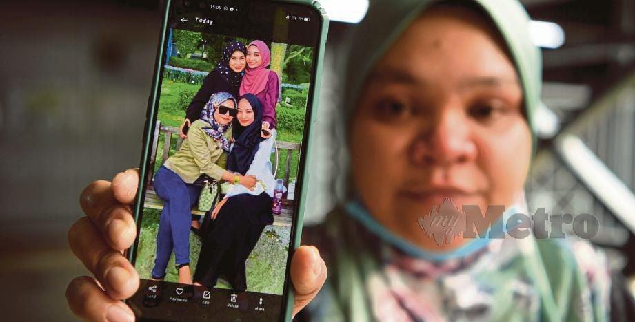 Nor Jamilah Ahmad menunjukkan gambar terakhir dirakam di Pulau Jerjak semalam oleh anak saudaranya Sharifah Fariesha Syed Fathi, 21, (duduk, kiri), yang maut dalam kereta akibat keracunan karbon monoksida di kawasan parkir sebuah stesen minyak di Sama Gagah. FOTO BERNAMA