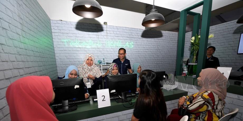 Presiden dan Ketua Pegawai Eksekutif Takaful Ikhlas General Berhad Eddy Azly Abidin (berdiri kanan) beramah mesra bersama pengunjung yang hadir ke kaunter Takaful Ikhlas selepas Majlis Perasmian Minggu Saham Amanah Malaysia (MSAM) di pekarangan Amanjaya Mall. FOTO BERNAMA