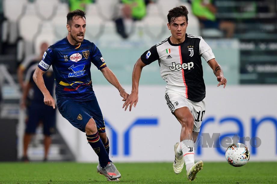 DYBALA (kanan) cuba melepasi halangan pemain tengah Lecce, Marco Mancosu ketika perlawanan berlangsung di Turin awal pagi tadi. FOTO AFP