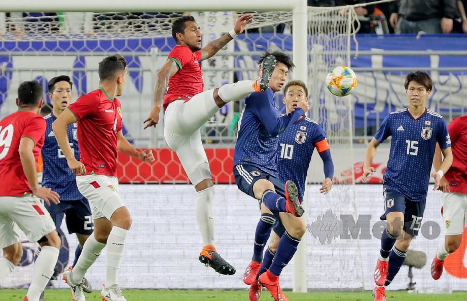 Pemain tengah Bolivia, Adrian Jusino (tengah) dan penyerang Jepun, Daichi Kamada (tengah kanan) bersaing merebut bola dalam perlawanan persahabatan. FOTO AFP.