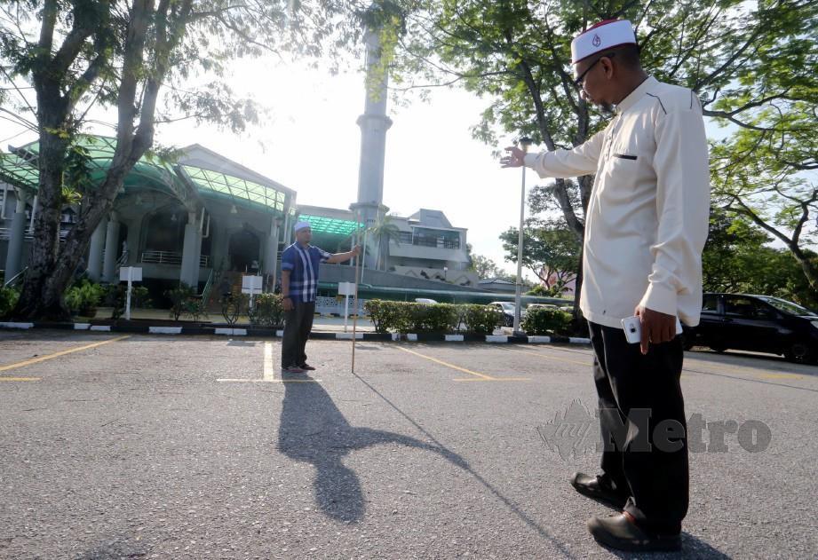 KETUA Imam Masjid Saidina Umar Al Khattab, Mohd Radhi Abdul Ghani (kanan) bersama Imam 2, Muhd Burhanuddin Othman memeriksa arah kiblat menggunakan sebatang kayu yang dipacak tegak pada jam 5:28 petang sempena fenomena Istiwa Adzam di perkarangan masjid itu, tahun lalu. FOTO Eizairi Shamsudin