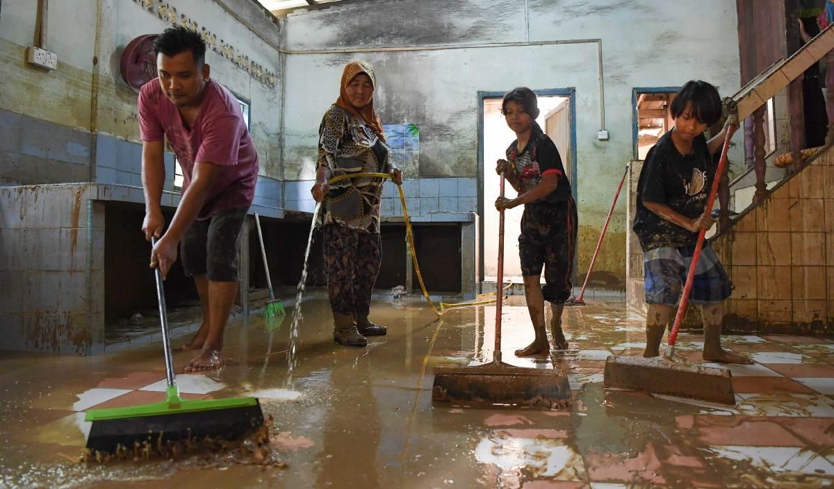 MANGSA banjir, Asmah Yaakop (dua, kiri) dibantu anak dan cucunya membersihkan rumah yang berlumpur berikutan dilanda banjir di Kampung Teladas, Air Putih. FOTO BERNAMA