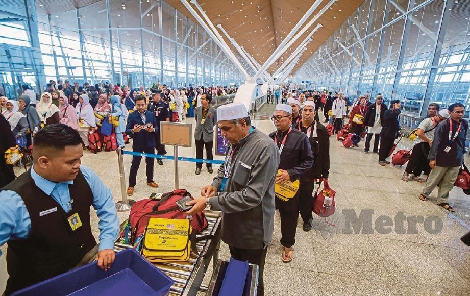 PETUGAS memeriksa beg jemaah haji sebelum menaiki pesawat. FOTO Luqman Hakim Zubir