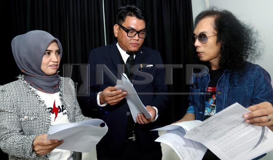 HATTA (kanan) bersama isteri, Azslender Abdul Aziz dan penguamnya, Faizul Mohd Nasir berbincang sesuatu pada sidang akhbar kes saman penganjur di Balai Berita. FOTO Halimaton Saadiah Sulaiman
