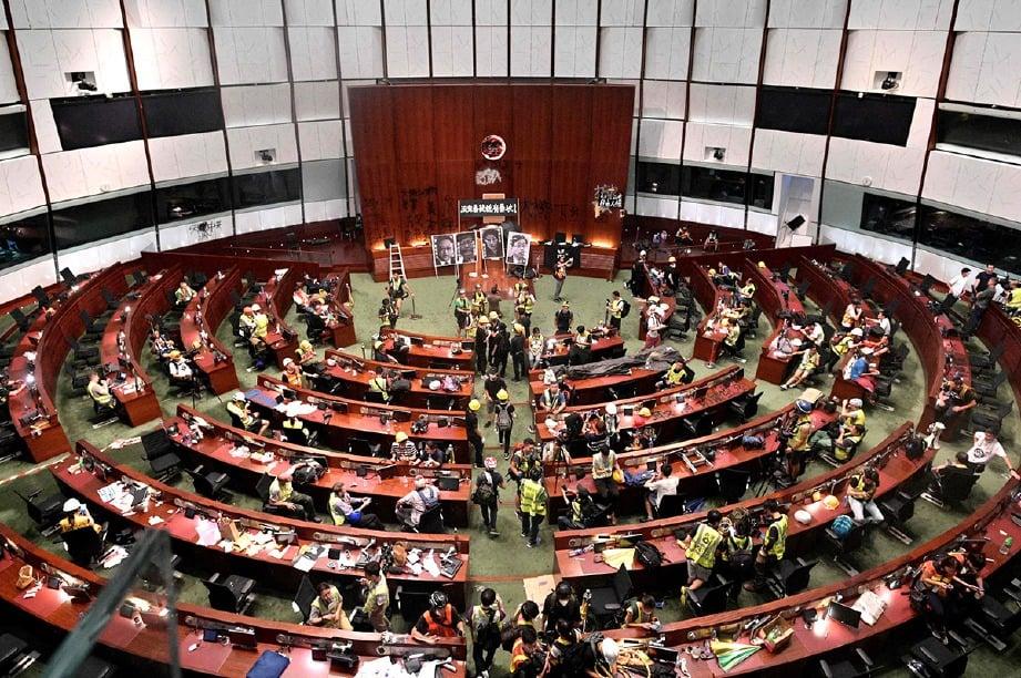 PENUNJUK perasaan dan pihak media menceroboh Parlimen Hong Kong petang semalam. FOTO AFP