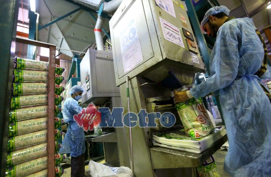 PEKERJA di kilang Syarikat Faiza membungkus beras keluaran beras Faiza di Kilang Syarikat Faiza. FOTO Rosela Ismail