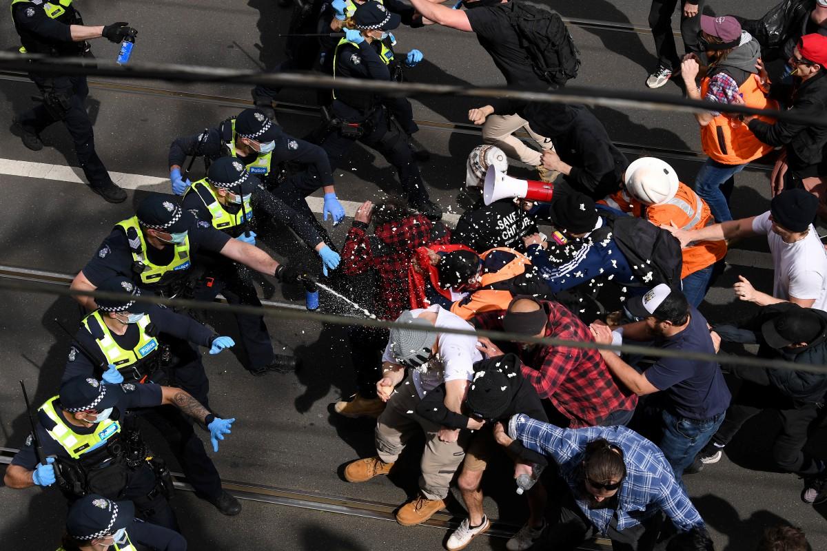 Anggota polis Victoria berdepan tindakan agresif peserta protes. - FOTO EPA