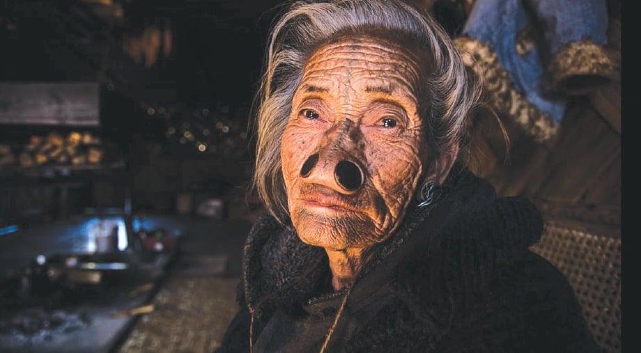 SEORANG wanita Apatani yang memakai penyumbat hidung dan mempunyai tatu di muka bergambar di rumahnya di India. FOTO Agensi