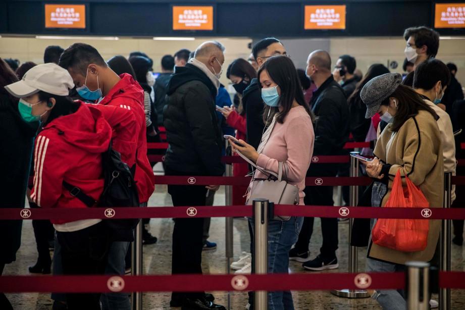 PENUMPANG memakai penutup hidung dan mulut beratur ketika membeli tiket di stesen kereta api laju dari Hong Kong ke China. FOTO AFP
