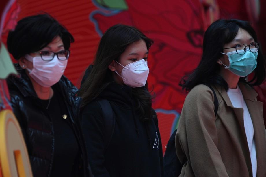 ORANG ramai memakai penutup mulut dan hidung ketika berjalan-jalan di Hong Kong. FOTO AFP