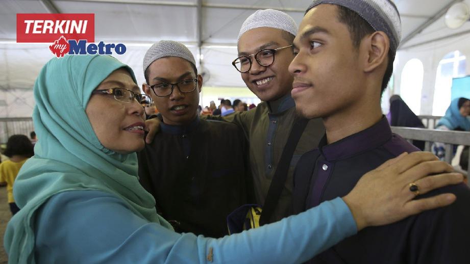 MUHAMMAD Asyreen (dua kiri), Muhammad Asyraf (dua kanan) dan Muhammaf Asyreef (kanan) diberi nasihat oleh ibu mereka, Asmah sebelum berlepas untuk menunaikan Haji. FOTO Sairien Nafis