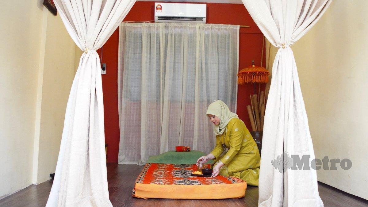 NOOR Khurshiah menyiapkan minyak dan tempat untuk ibu lebih selesa mengurut.