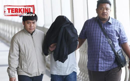 TERTUDUH dibawa oleh anggota SPRM di Mahkamah Sesyen Kuala Lumpur. FOTO Yazit Razali